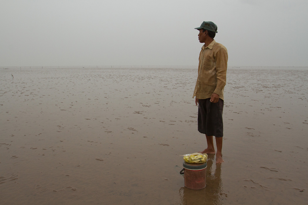 A local man returns from collecting small fish and crustaceans in the mudflats.