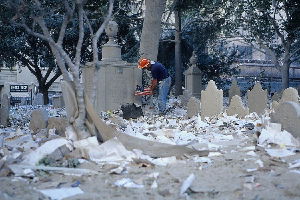 A rescue worker tries to remove dust from an American flag on the debris covered cemetery of St. Paul's Chapel