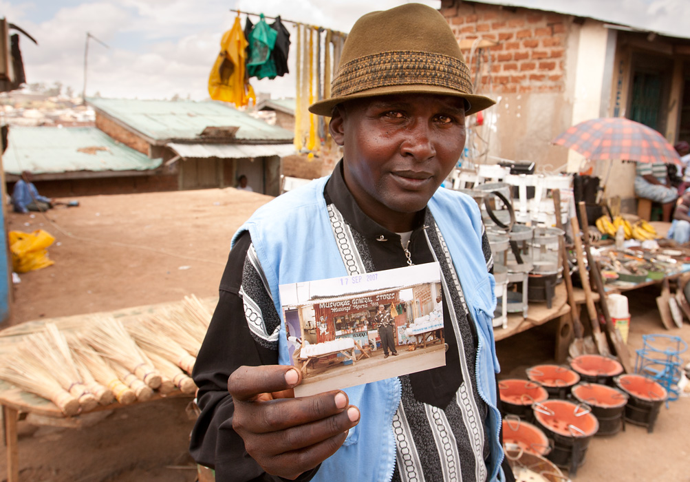 A man in Mathare Slum in Nairobi, Kenya shows a picture of his store, which was destroyed during ethnic violence.