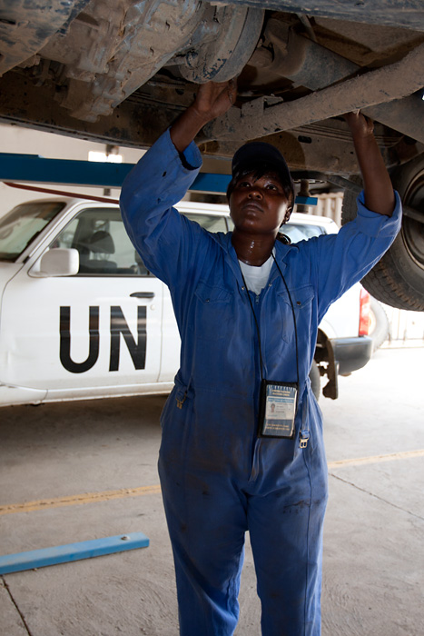 A UN volunteer car mechanic works on a vehicle at a repair shop in N'Djamena, Chad