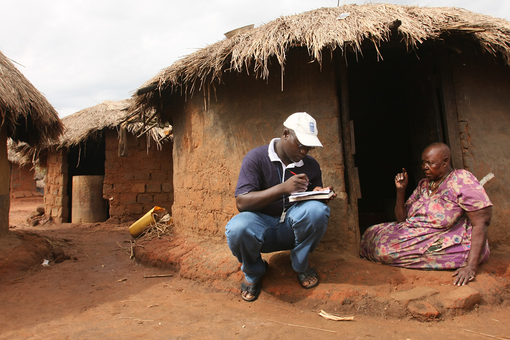 UN Volunteer Gerald Janani Loum speaks to an elderly woman at an IDP camp in northern Uganda