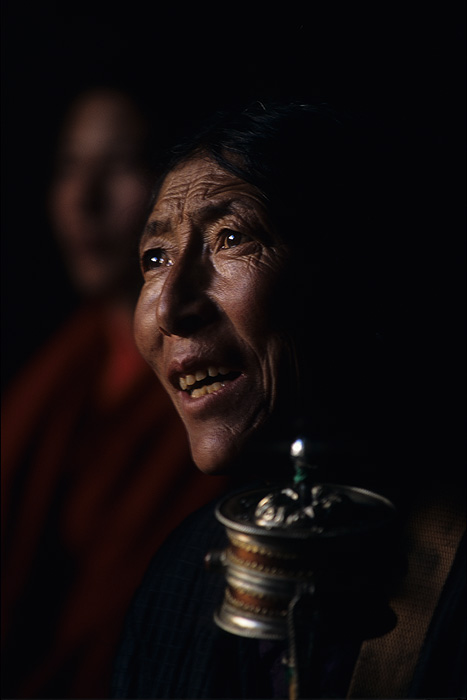 A pilgrim, holding a prayer wheel, watches the monks at the Jokhang monastery