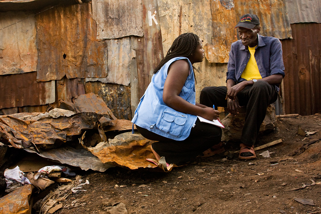 Community volunteer Triza Awino interviews a man who lost his home to a fire in Kibera Slum, Nairobi