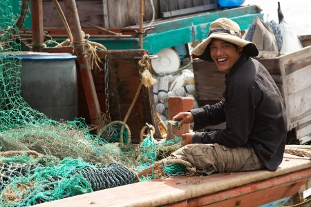 Fisherman fixing his net on a boat near Mui Ca Mau, Vietnam.