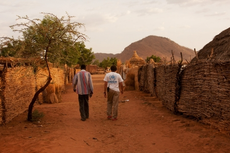 A UNHCR-worker and his local partner walk through a refugee camp in Goz Beïda, Chad.