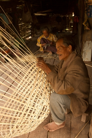 An old couple weaves bamboo baskets in their home