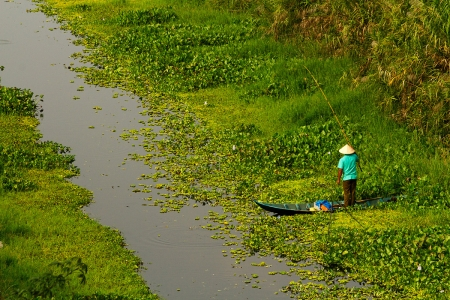 A fisherman stands in his boat in a canal in Kien Giang Province, Vietnam