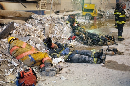 Exhausted firefighters sleep in the debris across the street from the World Trade Center site