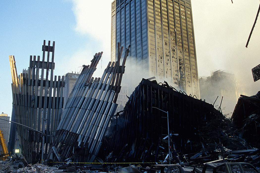 A section of the outer façade of the World Trade Center tower (left) has ripped off a section of WTC 4 (right) as it fell.